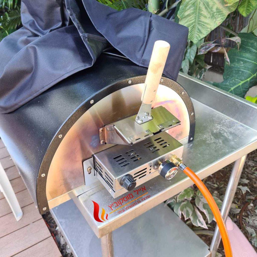 צינור גז כתום מחובר להצתה לשחרור גז בטאבון גז ביתי