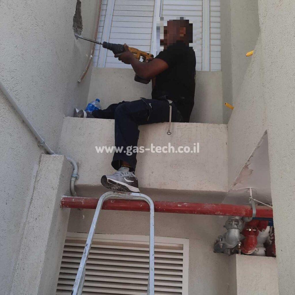 טכנאי גז קודח בקיר לגילוי צינור גז שניזוק